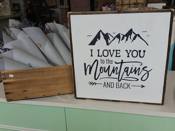 I Love You To The Mountains And Back — A perfect sign for an adventure, mountain loving member of the family! Details: - Approximately 14 x 14 x 1. - Hand stenciled on premium pine plywood cased is a dark brown wood frame. - Color: White, Black. - Painted. No vinyl is used. - Sanded to be slightly rustic. - Sealed with satin (matte) sealant for added durability  **Picture may vary slightly from the one you receive due to character variances in the wood**  Hanging Hardware: Framed sign hangs…