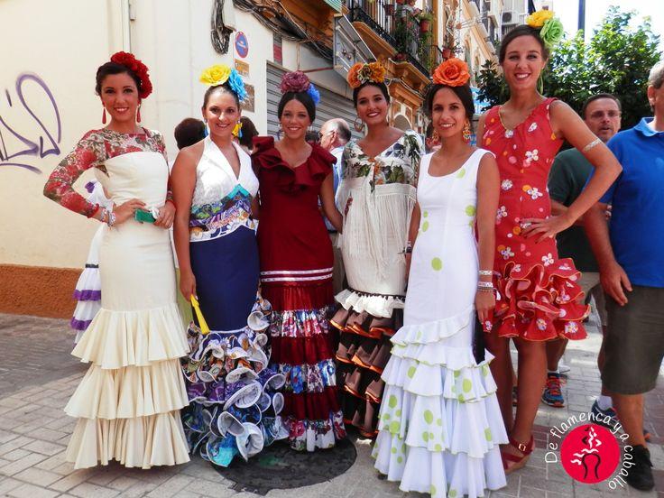 Grupo de mujeres vestidas de flamenca con vestidos de volantes blancos, traje de gitana beige, vestido canastero burdeos, vestido de flamenca corto en la Feria de Malaga 2015 en la Romeria de la Victoria