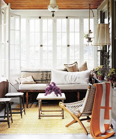 This sunroom looks so cozy...love the plant in the corner hanging by rope