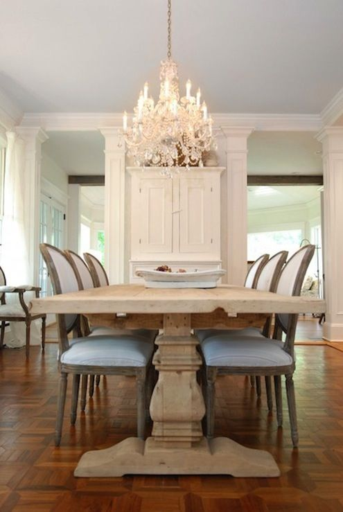 Beautiful modern French dining room design with Restoration Hardware Trestle Salvaged Wood Extension Dining Table & Vintage French Round Upholstered Side Chairs, parquet wood floors and crystal chandelier.