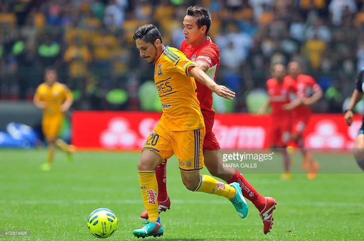 Edgar Solis (L) of Tigres, vies for the ball with Gerardo Rodriguez (R) of Toluca during their Mexican Clausura tournament football match at the Nemesio Diez stadium on May 10, 2015, in Toluca ,Mexico