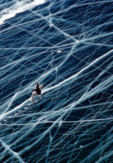Riding a horse across a frozen lake in the Pamir mountains of Tajikistan
