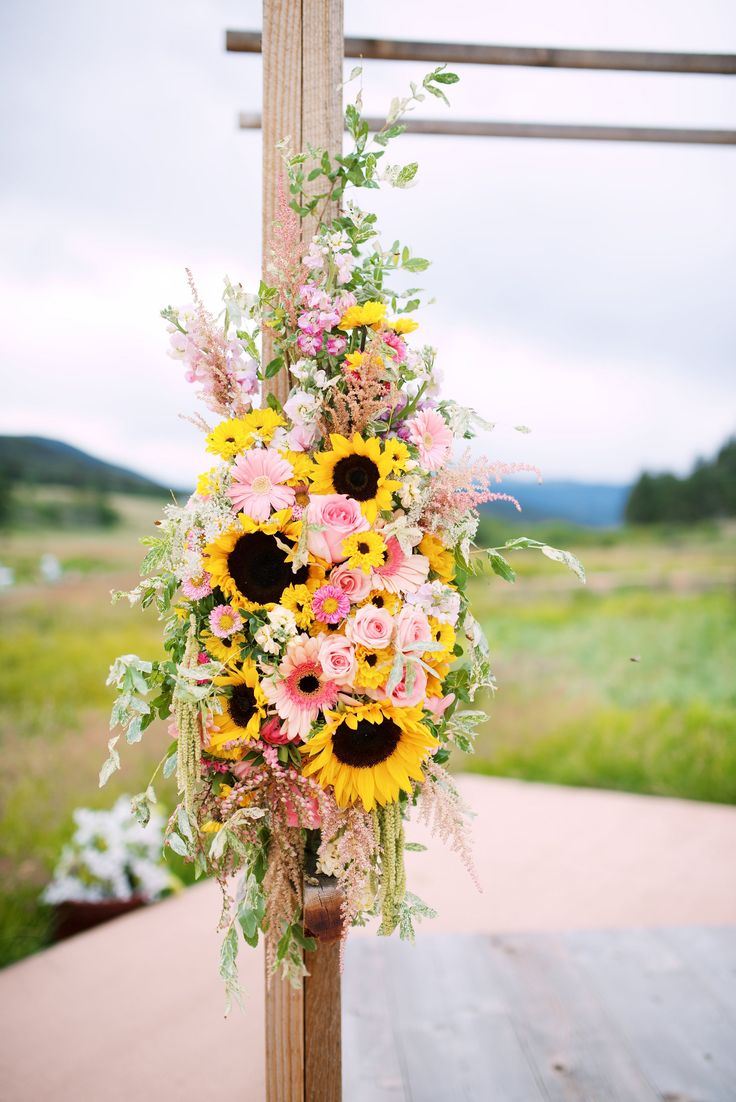 Arch spray of pink and yellow featuring sunflowers, gerber daisies, ranunculus and roses by Pink Posey Design