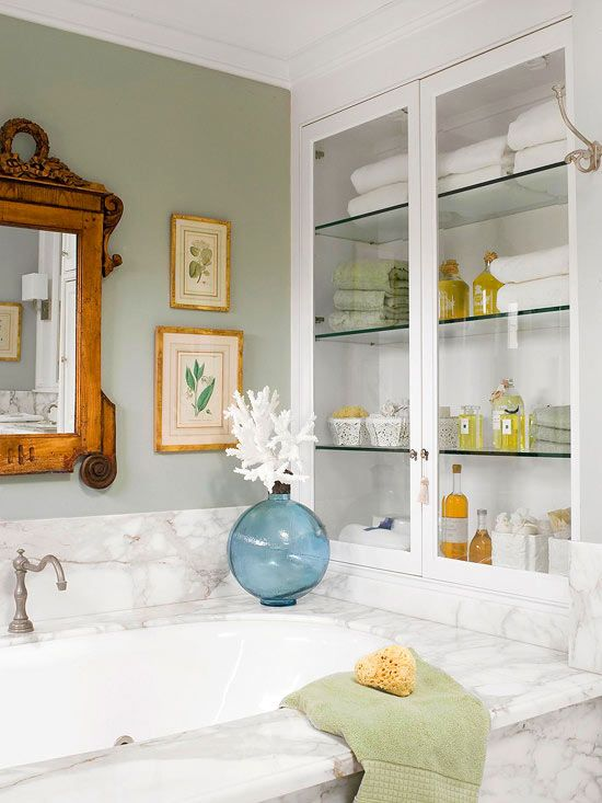 A built-in cabinet behind a soaking tub keeps towels, soaps, and sponges within reach. Glass doors and shelves make the cabinet feel light and airy.
