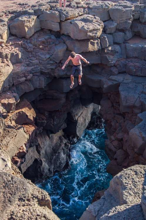 Man Jumping Off of Cliff into Ocean Opening Surrounded by Rocks at South Point on the Big Island Of ... - Julie Thurston Photography/flickr Editorial/Getty Images/Getty Images