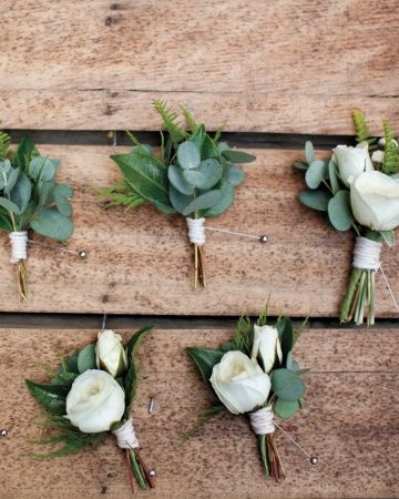Simple boutonnieres with white ranunculus and heavy use of greens