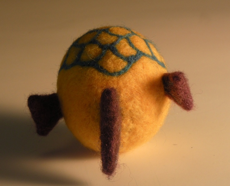 the back view of a yellow felt fish with purple fins.