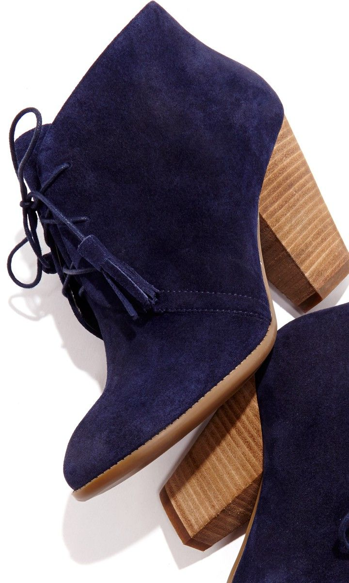 Soft suede lace up bootie with tassel detail on laces, rounded toe and a stacked heel.