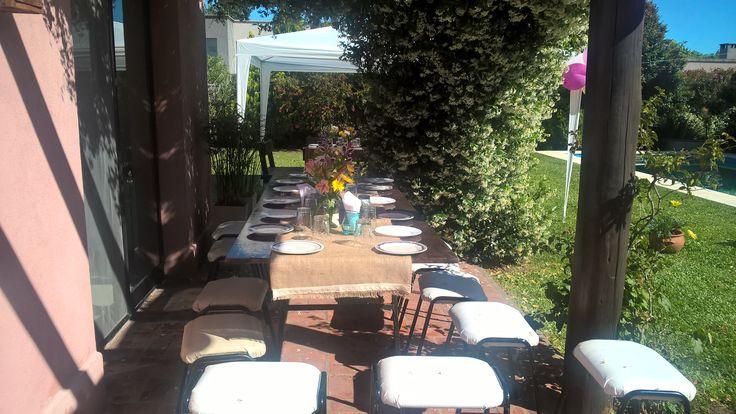 Mesa rústica con Camino de arpillera y puntillas de hilo, muchas flores en frascos de vidrio