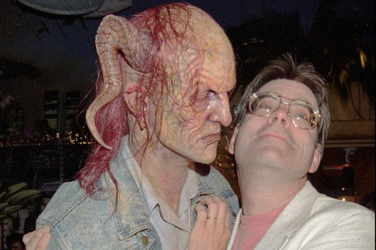 Stephen King with a mask of the character Randall Flagg from The Stand.