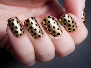 Gold and black polka dots nail art