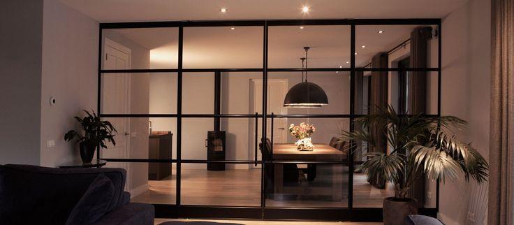 Bij een relatie in Wageningen hebben we een set stalen taatsdeuren met twee vaste zijpanelen mogen plaatsen. Deze glazen wand vormt een afscheiding tussen de woonkamer en de eetkamer.