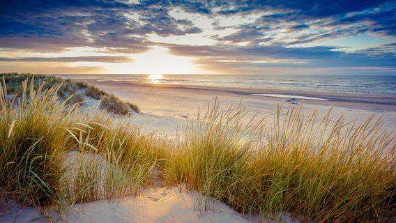 Ik zat net op deze duin te wachten, totdat de zon onderging. Met dat ik daar zat kwam de zon door de wolken en bescheen nog net even het puntje duin vlak voor me. Dit resulteerde in dit beeld. Ook de 2 wandelaars op het strand geeft de diepte van de foto weer.