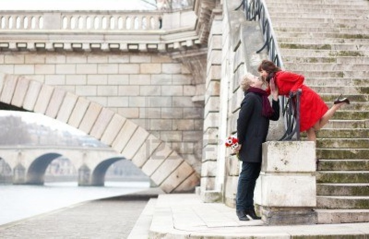Beautiful romantic couple kissing on a Parisian embankment at spring or winter Stock Photo