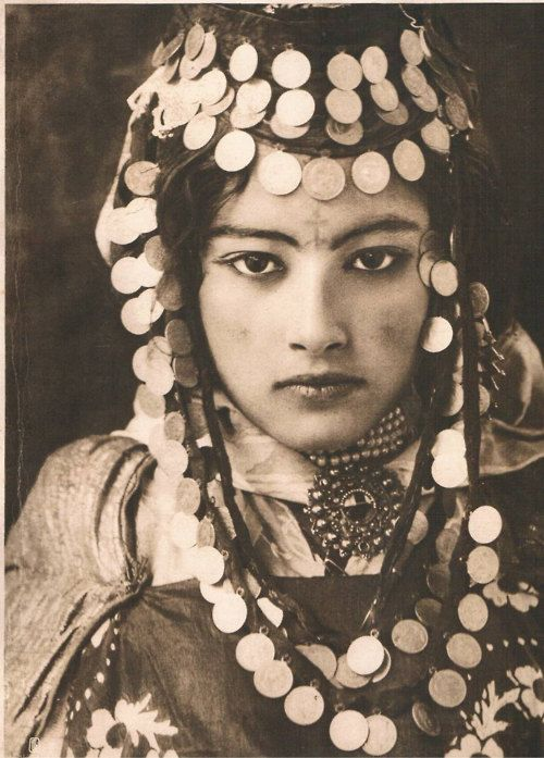 Algerian woman of the Ouled Naïl, a tribe in which the women travel from city to city to earn their income through dance & more intimate entertainment. After earning enough money or reaching a certain age, the women returned to their native villages to marry. Their costuming style is reflected in modern tribal belly dance styles.