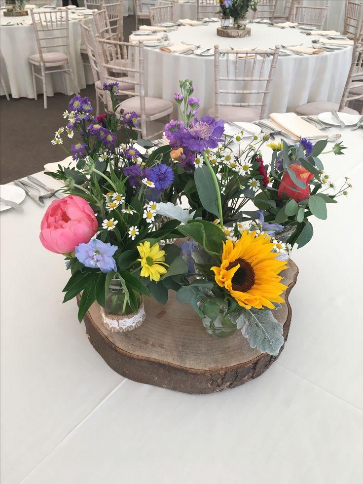 Jam Jar Arrangement:Sunflower, Mini Daisies, Silver Leaf, Scabiosis, September Flower, Coral Peonies, Burnt Orange Roses Cerise Pink Aster, Eucalyptus, Purple Stock on a log base