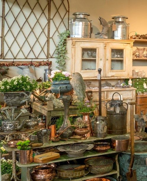 A plethora of vintage and antique garden paraphernalia - small decorative statuary, potting benches, copper pots and watering cans galore.
