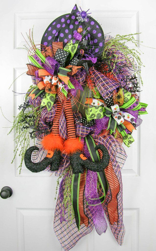 "Let the Halloween madness begin with this bold and beautiful witchy wreath. An extra large designer quality plaid deco mesh base with two 36"" gathering bows and two multi-patterned Terri Bows with nin"