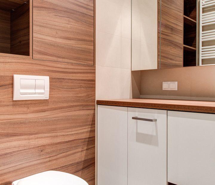Aranżacja łazienki z drewnem. Obudowa toalety, blat wokół umywalki oraz szafki wykonane z drewna o tym samym odcieniu. Całość uzupełniają białe elementy ceramiczne.