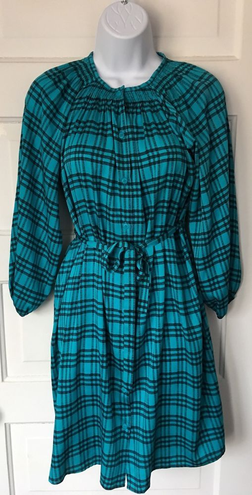 "Button down shirt dress with waist sash by Tucker. Blue and black plaid. Size medium. Sleeve: 20"". Shoulder to shoulder: 15"". Length: 35.5"". 