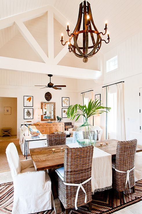 source: Elizabeth Newman Interior Design. Tropical island dining room with BoBo Intriguing Objects 8 Light Wine Barrel Chandelier, salvaged wood rectangular dining table, seagrass side dining chairs, white slipcover captain dining chairs, recycled glass vase and beadboard sloped ceiling.