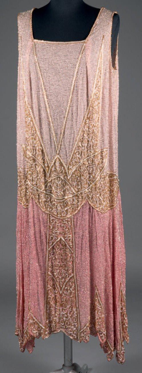 MOLYNEUX (attribué à) Robe perlée, vers 1926. Mousse-line de soie bi-colore rose tendre et rose bonbon, constellée de perles tube argent. Belle broderie de fleur de lotus et rinceaux en perles nacrées et or se déployant en pointe sur le corsage, les hanches et la jupe à ourlet asymétrique