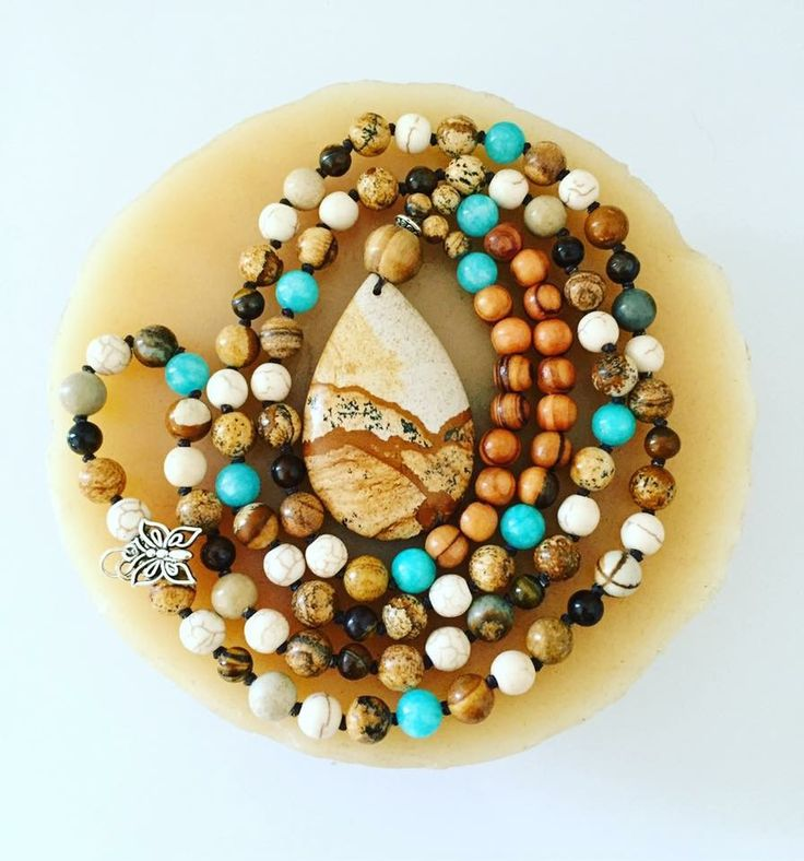 """108 bead Mala with 8mm Olive Wood, Picture Jasper, Magnesite, Brazilian Aquamarine and Tiger Eye beads. A teardrop Picture Jasper focal and butterfly charm give this hand-knotted Mala the perfect finishing touches!  Hangs at just under 21"""""""