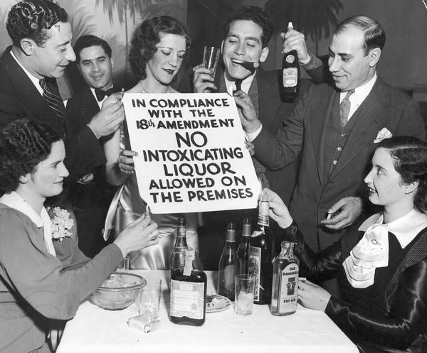 "Revelers celebrate the end of Prohibition, 1933. This unidentified group of drinkers celebrated the repeal of Prohibition by posing for a photo in which they burned a sign reading ""In Compliance With The 18th Amendment, No Intoxicating Liquor Allowed On The Premises."" Photograph by Frank Scherschel."