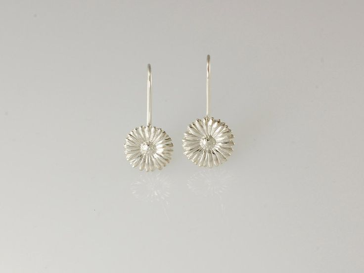 -Daisy Drop Earrings- NZ$89- Silver. Our daisy drop earrings make a perfect gift for a loved one. Do you remember sitting in the summer sun creating long daisy chains? Sadly they only last a short time but our silver daisies are everlasting! The daisy collection includes pendants, hoops earrings, studs and the daisy chain necklace. Daisy size 12.5mm. Earrings are 28mm long approx. Jewellery made @jewelbeetle in Nelson, New Zealand.