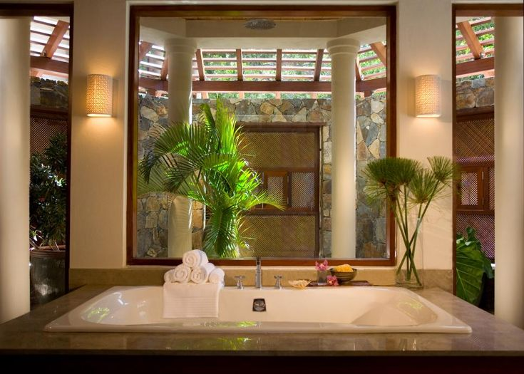 This spa-like bathroom is flooded with natural light as a result of the slatted rooftop, allowing a touch of the outdoors to peek its way through. A drop in bathtub surrounded by neutral stone and tropical plants provides a spot for relaxing, while a large window frames a glimpse at the stone walls in the adjacent room.