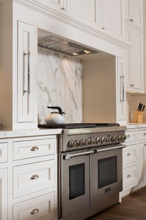 Beautiful kitchen features a nook filled with a Thermador stove and a marble backsplash flanked by pull out spice racks under a vent hood concealed by faux cabinets.