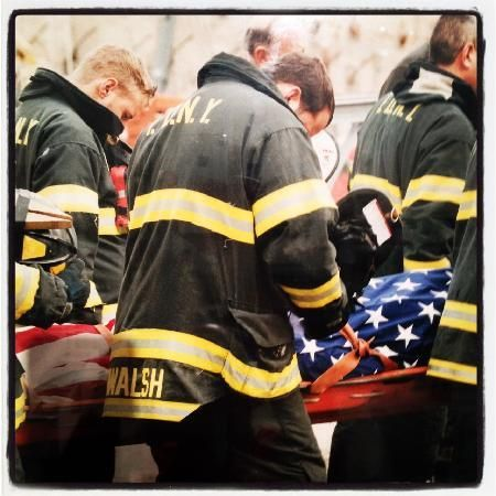 Honor.Guard - carrying out a body of a fallen FDNY brother from The Pile. Notice that not one is wearing his helmet - they found one of their brothers...So they removed their helmets in honor...