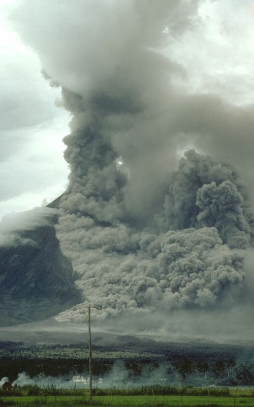 Pyroclastic flow sweeps down the side of Mayon Volcano, Philippines, during an explosive eruption on 15 September 1984. Note the ground-hugging cloud of ash (lower left) that is billowing from the pyroclastic flow and the eruption column rising from the top of the volcano.  Credit: Photograph by C. Newhall on 15 September 1984.