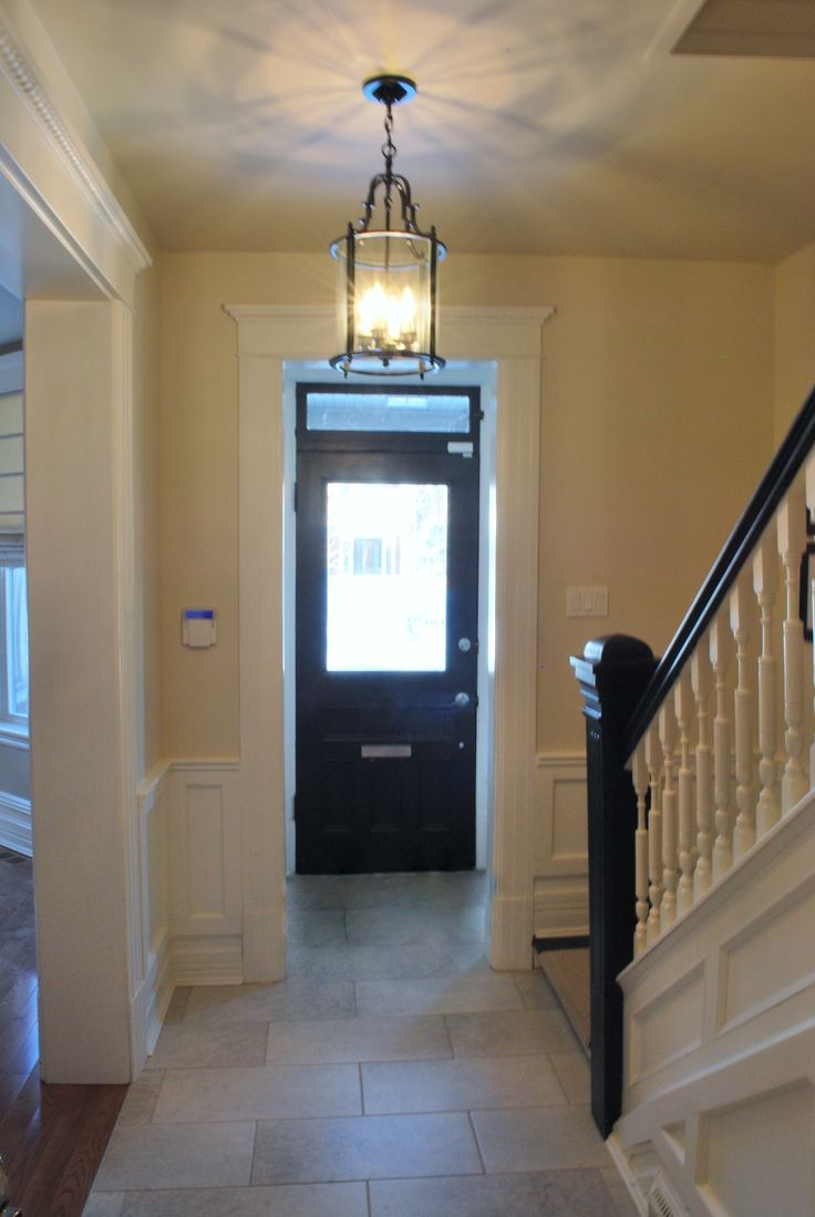 Century old house gets a whole new entrance from tiles to lighting while keeping the authentic staircase and original door. This is where the original trim meets the new wainscotting. Can you tell where the 'old' stops and the 'new' begins?