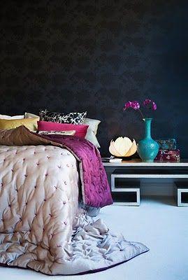 Esta habitacion tiene paredes negros y un pisa blanca.  La cama es muy grande y tiene muchas almohadas.  Un mesa pequena tiene flores al lado de la mesa.