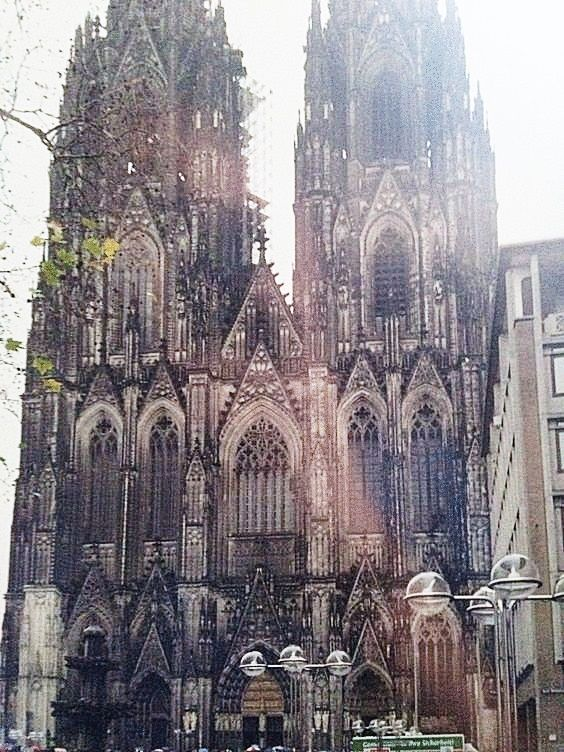 GERMANY –  West entrance to Cologne Cathedral (Kölner Dom) at Domkloster 4, Cologne (Köln), North Rhine-Westphalia. At the bottom left of this picture is the Kreuzblume, the finial model of the cathedral's towers, that is displayed on Domplatte in front of the cathedral. https://www.google.ca/maps/place/Cologne+Cathedral/@50.9412818,6.9495267,15z/data=!3m1!5s0x47bf25baabc20433:0x312b7d4db7d02b48!4m5!3m4!1s0x47bf25a5369c3d2f:0x29ec913896e3a9c6!8m2!3d50.9412784!4d6.9582814?hl=en-CA