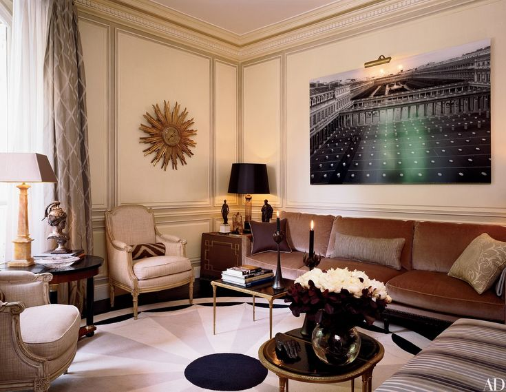 In a Paris apartment, a circular carpet from Galerie Diurne, designed by the home's decorator, Jean-Louis Deniot, simplifies the five-sided living room. A 20th-century gilt-wood sunburst clock echoes the carpet's pattern, while William Curtis Rolf's large-scale photograph of the Palais-Royal provides a powerful, if illusory, Paris view.