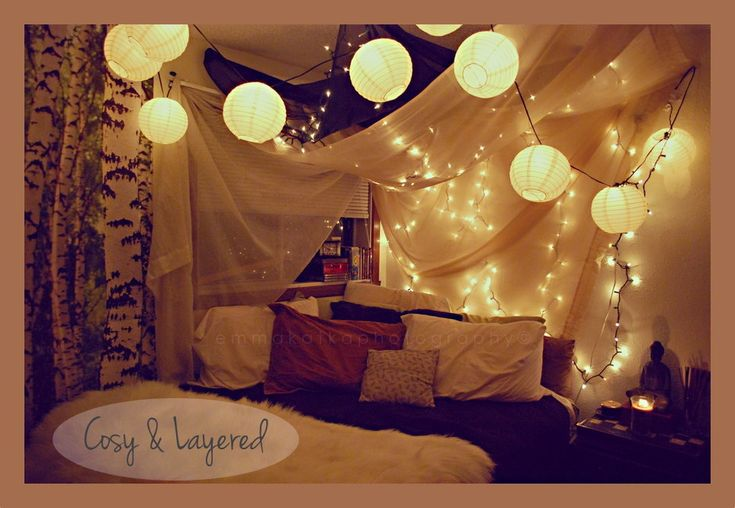 This reminds me of a child's fort but in an adult version.  Paper lantern, faerie lights, trees on the wall, lots of pillows, shrine, fur.