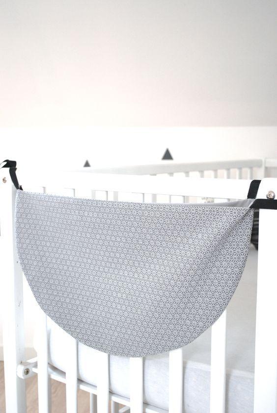Hamac de rangement gris et blanc aux motifs graphiques. Le hamac se noue avec 2 rubans noirs, cousus à chaque extrémité Doublure grise assortie Un accessoire indispensable pour ranger les petites affaires de bébé Largeur : 55 cm
