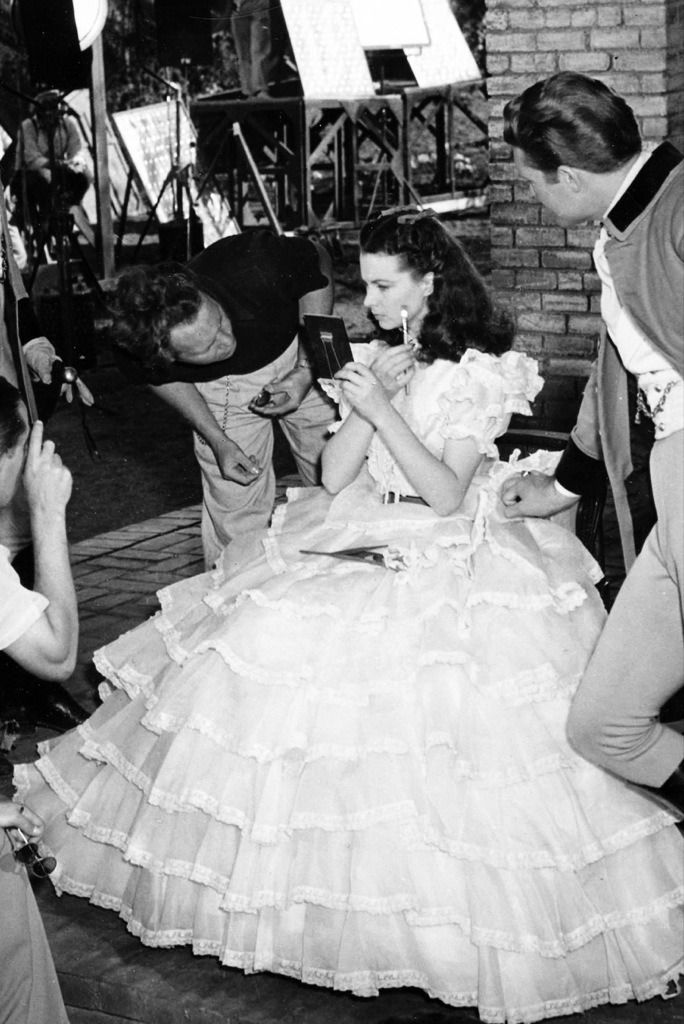 Vivien Leigh touches up her make-up for the opening scene on the set of GONE WITH THE WIND (1939). The actor standing in costume at the right is George Bessolo, who played one of the Tarleton twins. He later changed his professional name to George Reeves and went on to play Superman on television in the 1950s.