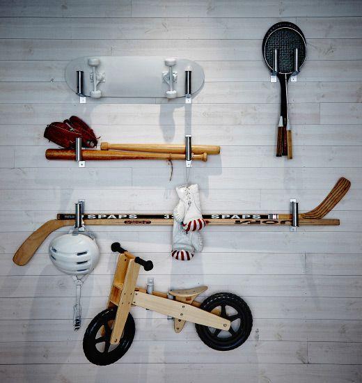 Porta-rolos GRUNDTAL fixados numa parede para apoiar vários equipamentos desportivos, bicicletas, etc.