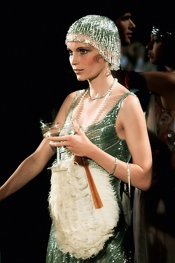 The Great Gatsby - Mia Farrow as Daisy Buchanan wearing a green sequined evening dress, matching fringed headpiece and feathered fan.