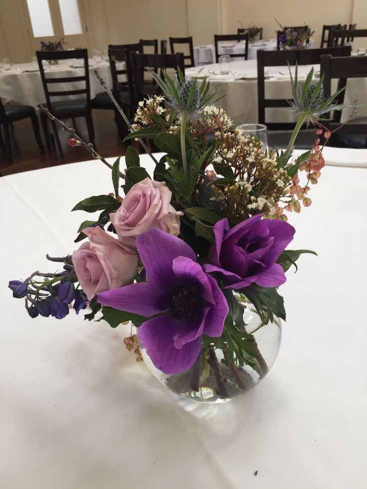 Loose and natural. Small fishbowls with anemone, rose, delphinium, sea holly and pieris