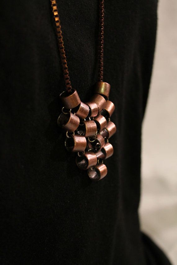 The pieces of this pendant have been hand cut and shaped from recycled copper tubing and linked in a pattern inspired by chainmaille to create movement. The pieces of copper tubing do spin and move comfortably with wear. The pendant does not hold a stiff shape. Jump rings tying the copper pieces together are solid sterling silver, the chain is copper as well and a patina was applied to the whole necklace. Copper pieces are coated with a permanent, clear spray jewelry laquer that will protect…