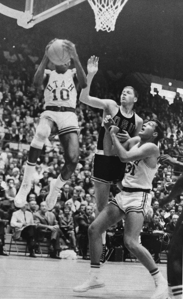 Merv Jackson (10) of the University of Utah goes high in the air to snag a rebound in the first half of the NCAA Far West regional playoff game against Oregon State University in Los Angeles, Calif., March 12, 1966.  Others are Jeff Ockel (31) of Utah and an unidentified Oregon State cager. (AP Photo/Ed Widdis)