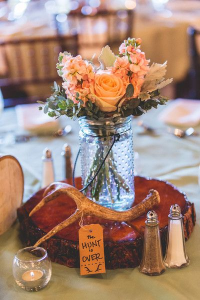 "Rustic peach wedding centerpiece idea - wooden slice with antler + clear glass jar filled with peach flowers with sign that says ""the hunt is over"" {Emily Joanne Wedding Films & Photography}"