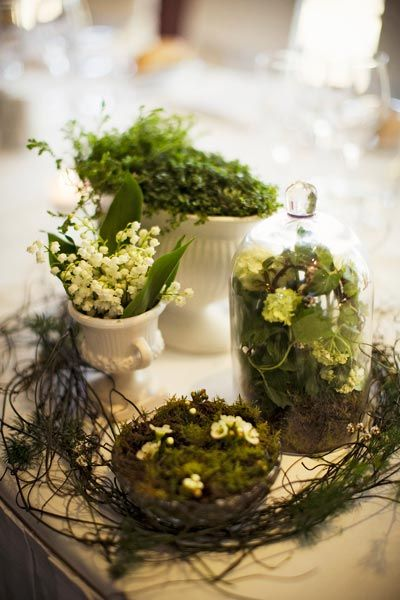Old white urns and paired with glass domes filled with blooms, foliage, moss, and occasional whimsical touches, like a bird or rabbit figurine hiding amongst the greenery created showstopping centerpieces.