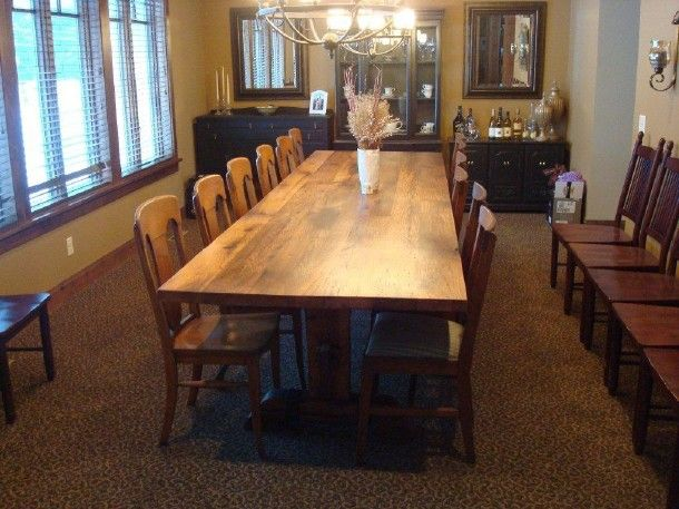 12 foot dining room table fits 12 to 14 people comfortably. It's a Red Oak on a iron adorned trestle base. It has great seating all the way around.