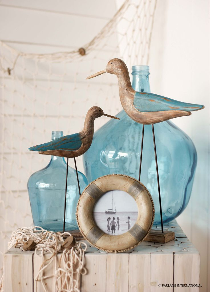 Blue glass bottles and nautical frames create a seaside theme