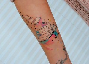 The Colored Book Tattoo with torn pages. The colored book tattoo is worth trying as it incorporates the combination of colors along with the open book. The pages of the book are torn and are flying in the air.